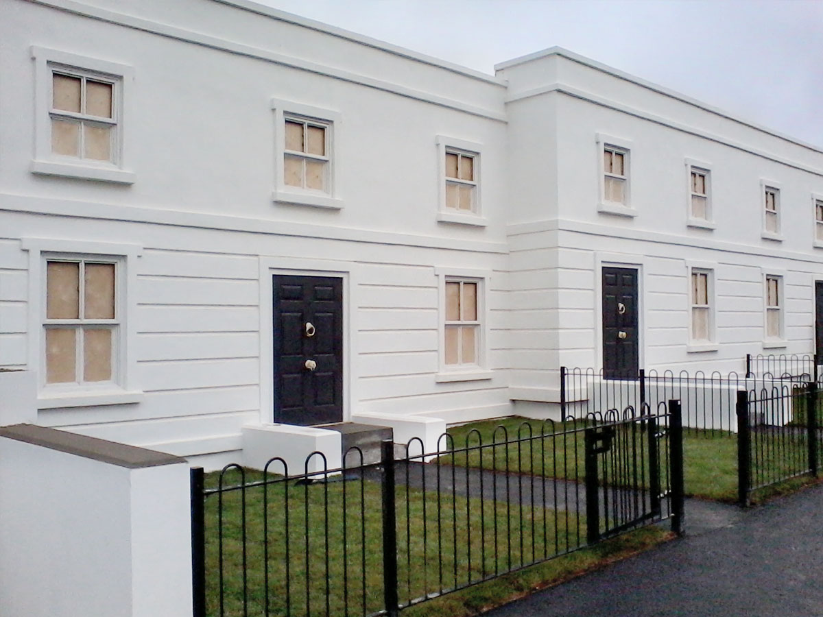 themed set of period white terrace building facade with black iron gates